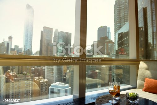 Window inside a cafe. On the table there are two cocktails. Out of the window there is a panoramic view of Upper Midtown Manhattan, NYC, USA