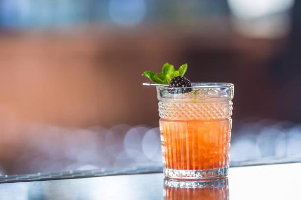 Cocktailgetränk Bramble mit schwarzen Beeren und Minze am Barcounter im Nachtclub oder Restaurant – Foto