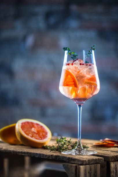cocktail drink on a old  wooden board. alcoholic beverage with tropical fruits red pepper herb and ice - grapefruit cocktail stock photos and pictures
