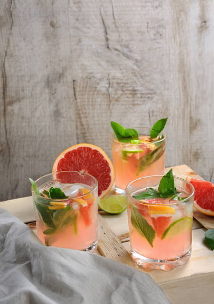 cocktail from london dry gin with juice from squeezed red grapefruit and leaves of delicate basil of lemon, lime slices and chilled ice cubes. - grapefruit cocktail stock photos and pictures