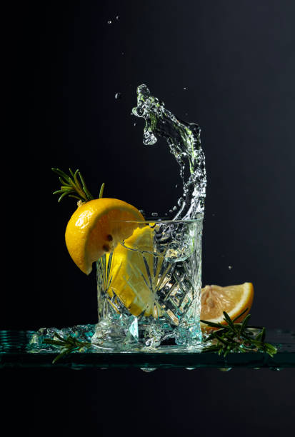 Cocktail gin-tonic with lemon and rosemary on a glass table. stock photo