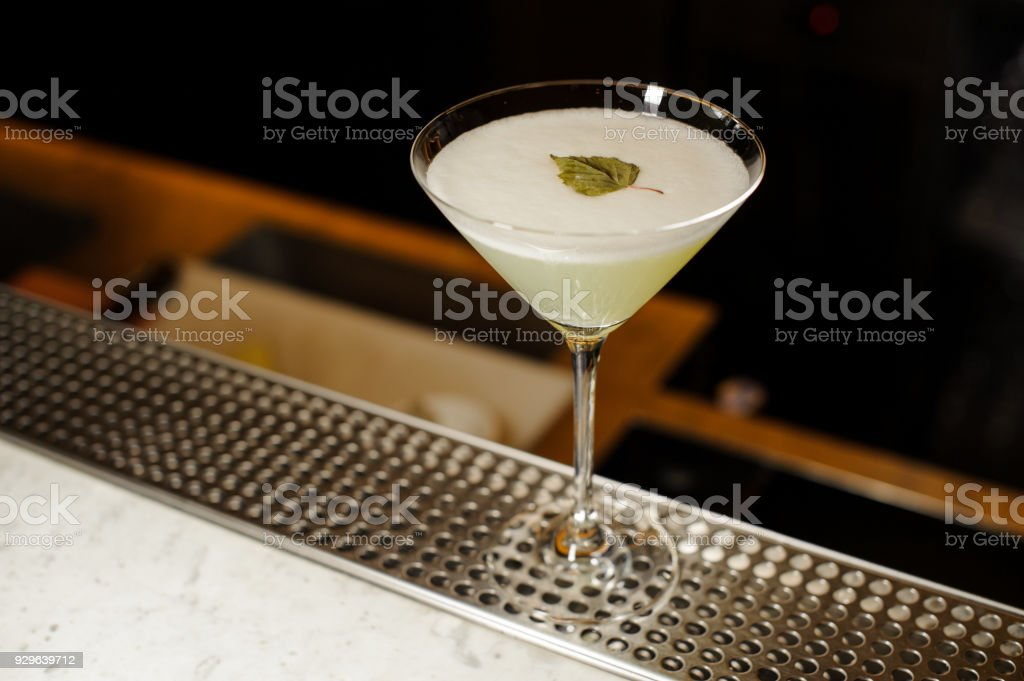 Cocktail glass filled with fresh alcoholic drink decorated with birch leaf stock photo