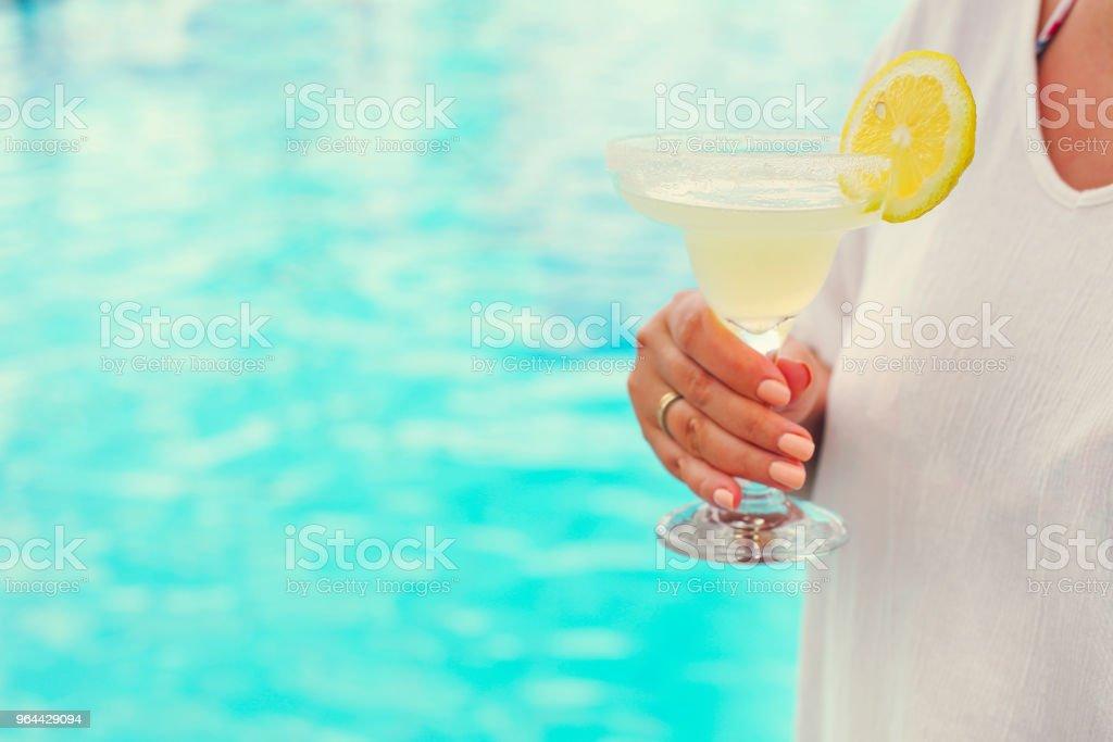 Copo de cocktail na mão da mulher perto da piscina - Foto de stock de Adulto royalty-free