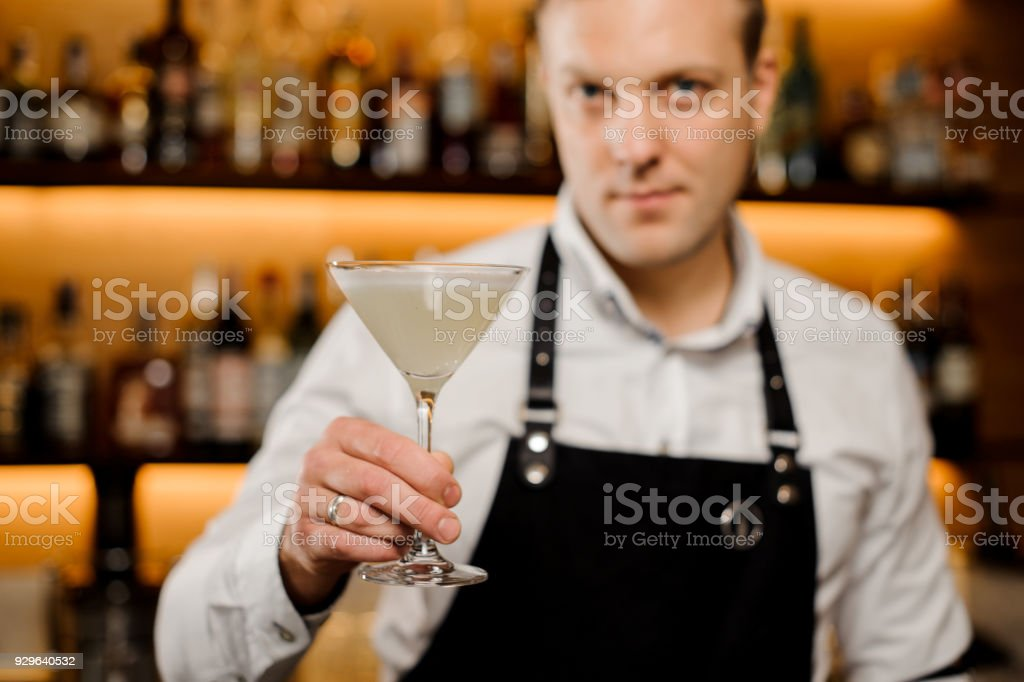 Cocktail glass with fresh alcoholic drink in bartenders hand stock photo