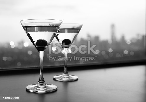 Black and white image of cocktail glasses with city view.