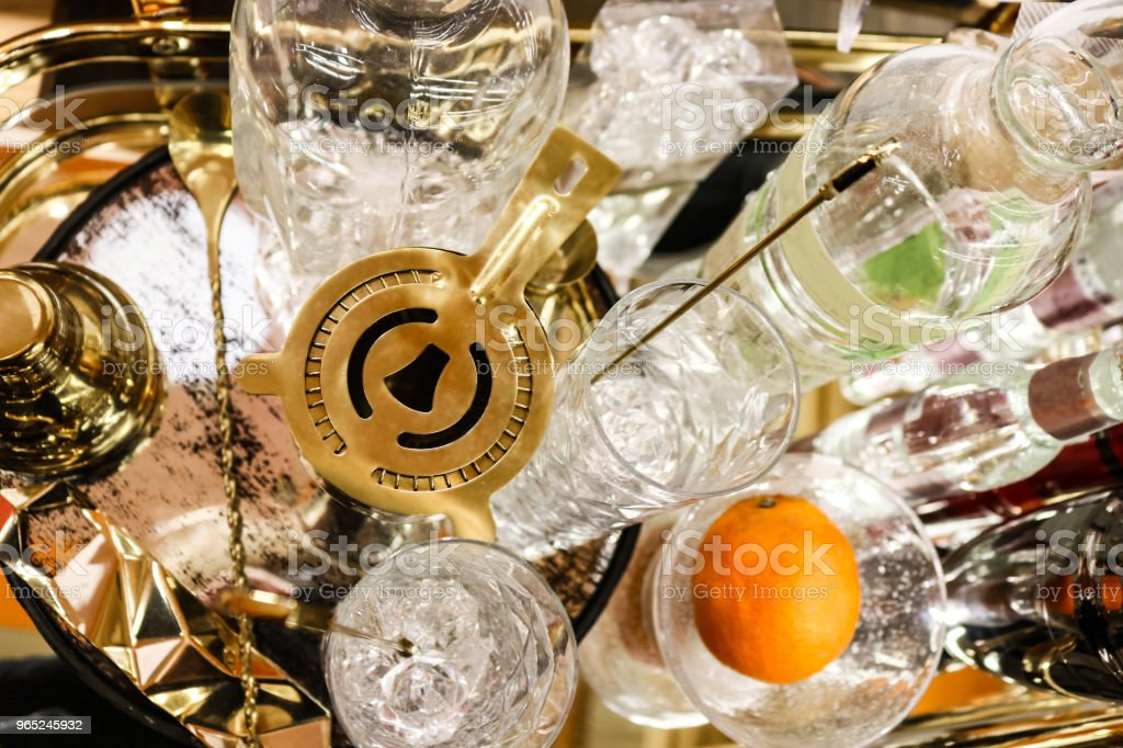 Cocktail hour - martini shaker on tray with various crystal glasses and bottles and an orange - top view and selective focus royalty-free stock photo