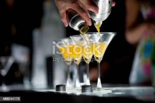 Photograph of human hands holding two cocktail shakers and pouring orange color cocktail into two martini glasses