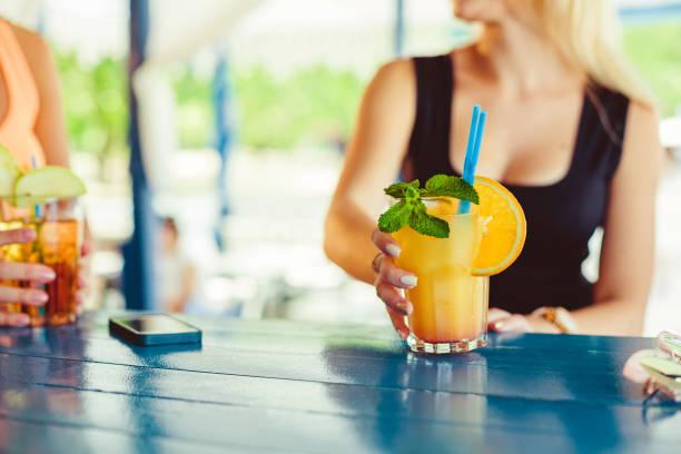 cocktail in der hand der frau auf der terrasse in der bar während der sommerzeit - dachschräge einrichten stock-fotos und bilder