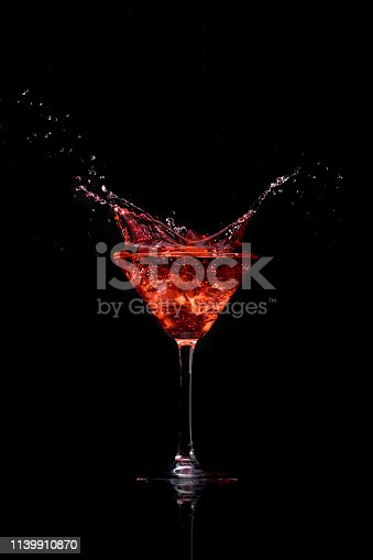 Ice drops into a a martini glass creating a splash
