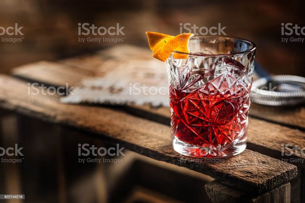 Cocktail Negroni on a old  wooden board. Drink with gin, campari martini rosso and orange stock photo