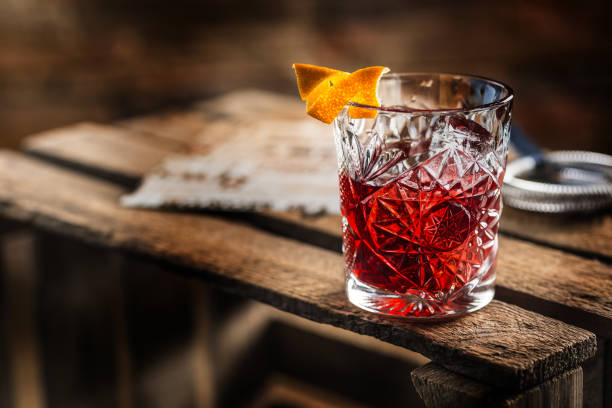cóctel negroni en una tabla de madera vieja. bebidas con gin, campari martini rosso y naranja - cóctel fotografías e imágenes de stock