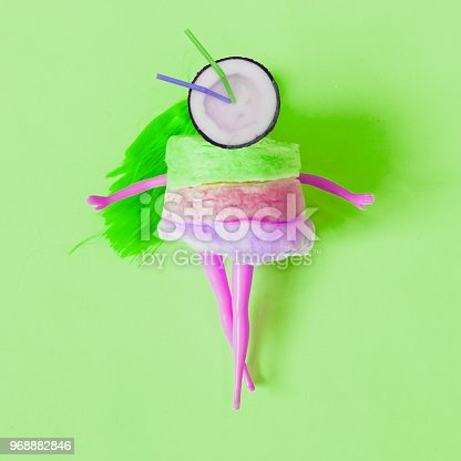 1125575680 istock photo cocktail of half a coconut instead of a head of the purple doll dressed in cotton candy. 968882846