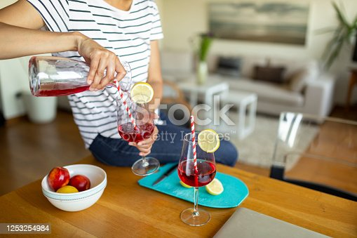 Close up photo of mixing and pouring a cocktail for herself, an African American woman is relaxing, enjoying and having fun at home with some alcoholic beverage