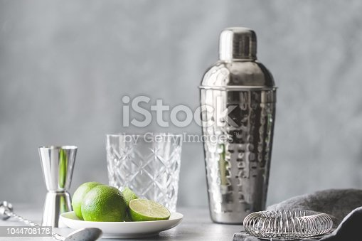 Cocktail shaker, strainer, bar spoon, glassware, measure and fresh lime on a table. The concept of preparing cocktails and alcohol beverages.