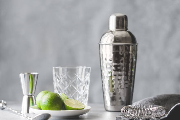 Cocktail shaker, strainer, bar spoon, glassware, measure and fresh lime on a table. The concept of preparing cocktails and alcohol beverages. Cocktail shaker, strainer, bar spoon, glassware, measure and fresh lime on a table. The concept of preparing cocktails and alcohol beverages. cocktail shaker stock pictures, royalty-free photos & images