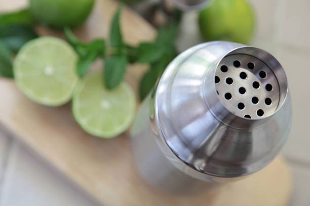 Cocktail shaker with limes and cilantro stock photo