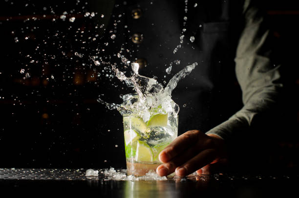 Cocktail splash with ice cubes and lime Cocktail splash with ice cubes and lime. Preparing of the delicious fresh cocktail on the bar stand bartender stock pictures, royalty-free photos & images