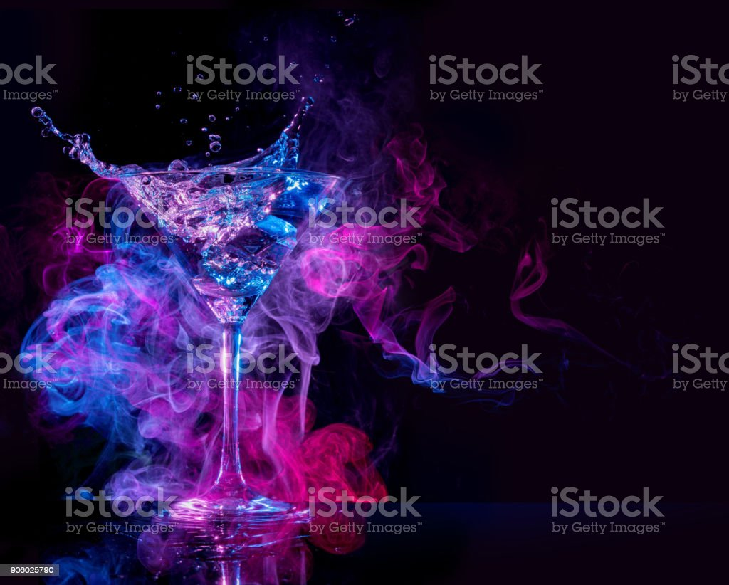 cocktail splashing in a smoky background stock photo