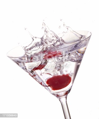 A red cherry splashing into a cocktail glass