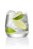 Cocktail with soda water, vodka or rum, ice and lime slice isolated on white background
