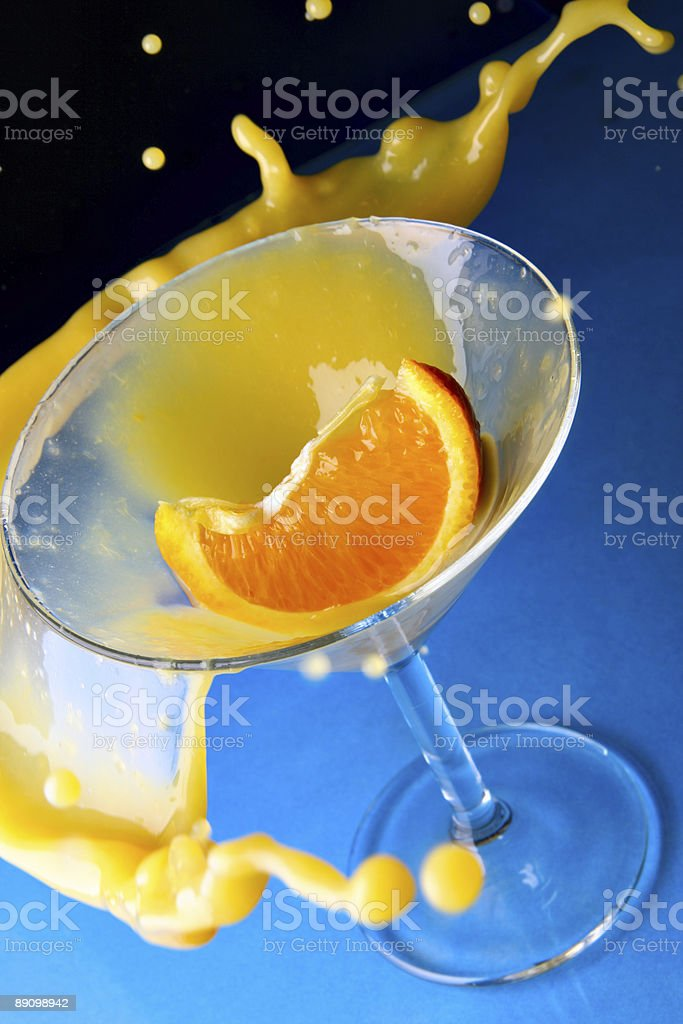 Cocktail with orange in glass and splashes stock photo
