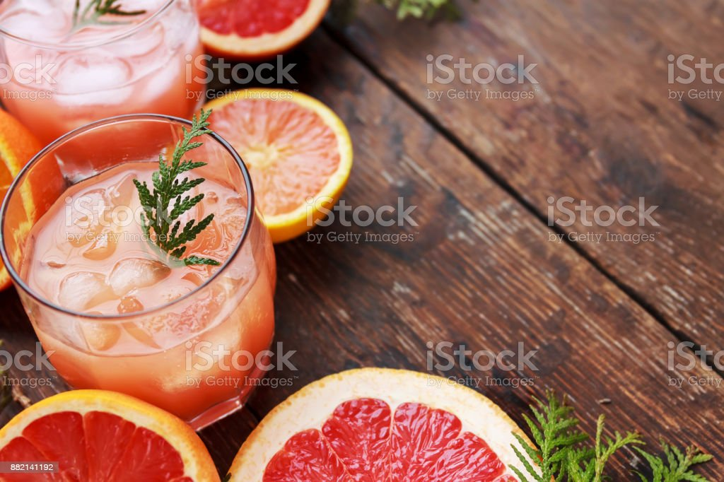 Cocktail with slices of grapefruit on a turquoise background. Grapefruit Martini stock photo