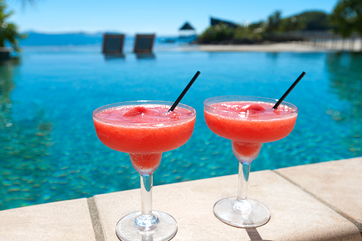 2 cocktails beside a resort swimming pool with beach in the background
