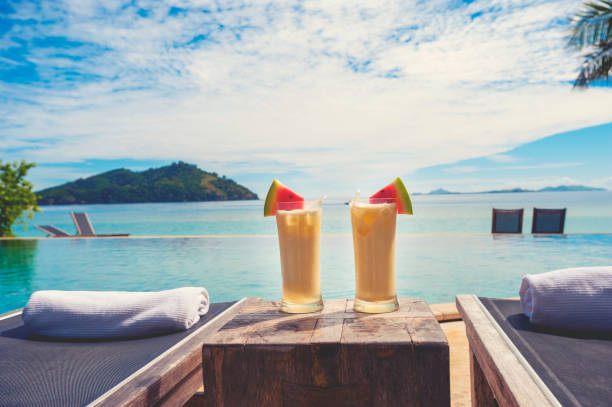 cocktails by the pool with beach in the background. - fiji stock photos and pictures