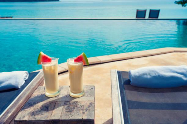 cocktails am pool mit strand im hintergrund. - ferienhaus thailand stock-fotos und bilder