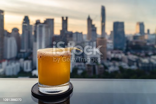 Cocktails glasses on the table in rooftop bar at Bangkok city view during sunset sky