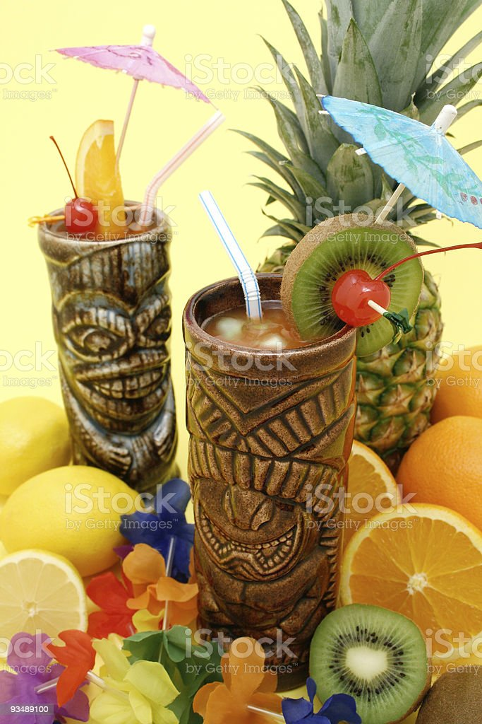 Cocktails in tiki glasses surrounded by fresh fruit stock photo