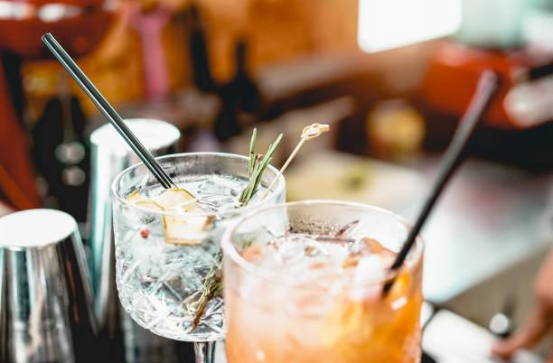 cocktails servis sur un comptoir préparé avec du gin, du romarin, du papier et du jus d'orange - boisson, vie nocturne, concept de style de vie - focus sur le verre cristallin supérieur - café boisson photos et images de collection