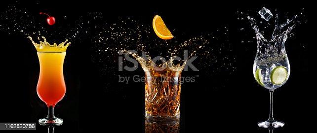 set of cocktail glasses splashing on black background