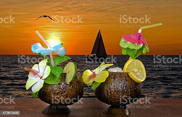 Photo of cocktails with sailboat at sunset