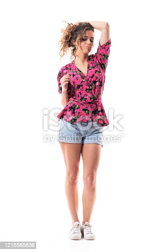 Cocky attitude confident sexy young woman holding hair in bun looking down and thinking. Full body isolated on white background.