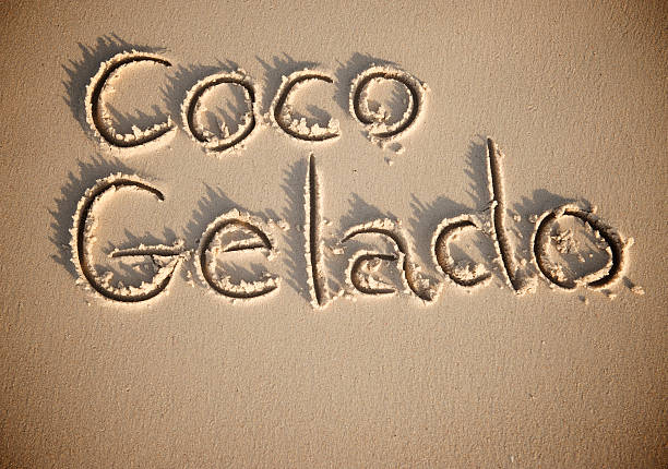 Coco Gelado Chilled Brazilian Coconut Message in Sand Coco Gelado message, Brazilian for chilled drinking coconut water, in textured sand gelado stock pictures, royalty-free photos & images