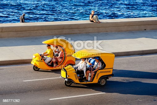 Havana, Cuba - March 17, 2015: Coco Taxis driving along the Malecon in Havana, Cuba. The three wheeled vehicle  is a common form of public transportation in the city of Havana Cuba.