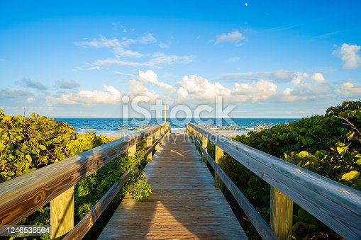 Boardwalk on beautiful Cocoa Beach, Florida with blue sky and clouds.