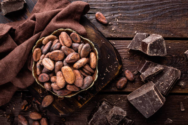 Cocoa beans and chocolate on wooden background stock photo