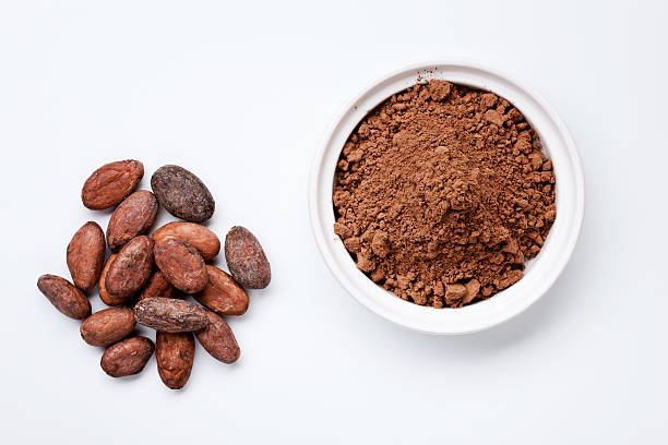 cocoa beans and grounded cocoa - cacaovrucht stockfoto's en -beelden
