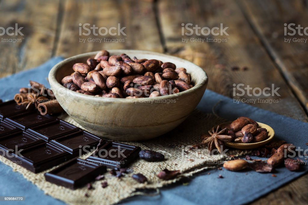 Cocoa beans, dark chocolate and spices on rustic wooden table stock photo