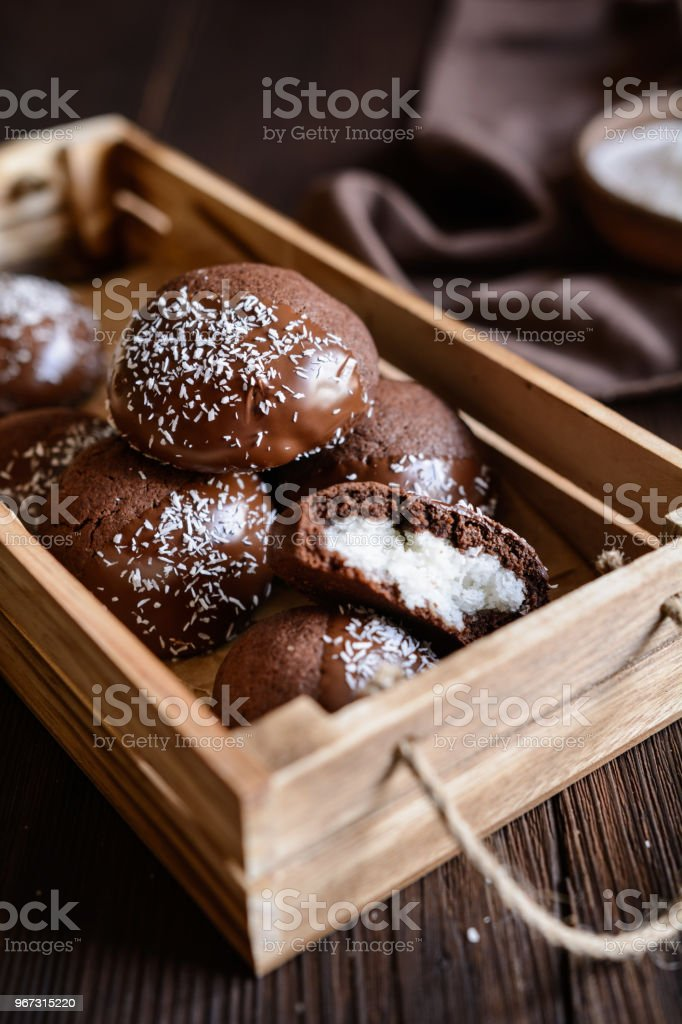 Cocoa biscuits with coconut filling, decorated with chocolate and grated coconut - fotografia de stock