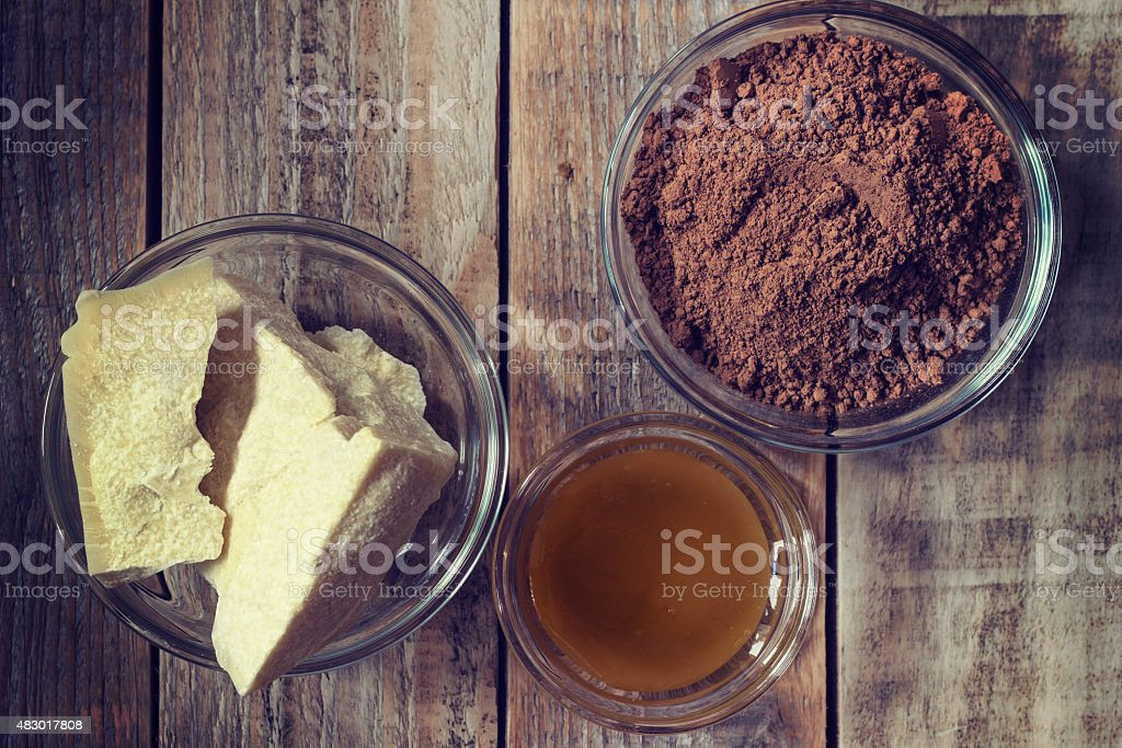 Cocoa butter, cocoa powder and honey on grunge wooden background stock photo