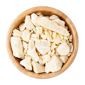 Cocoa butter in a wooden bowl isolated on white. Top view.
