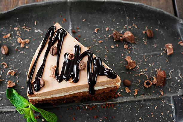 cocoa cheesecake and chocolate sauce, black plate - käsekuchen kekse stock-fotos und bilder