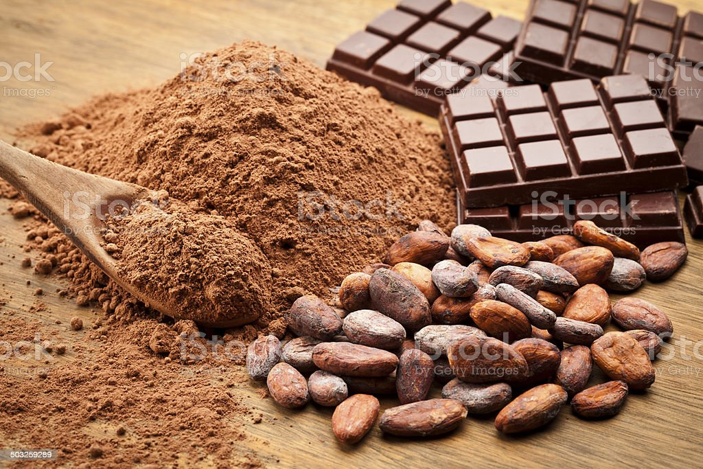 Cocoa in different presentations on wood table Cocoa Beans and Cocoa Powder with Chocolate Bars on Wood Table. Bean Stock Photo