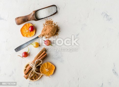istock Cocoa powder in a spoon with cinnamon and dry sitrus. A high key. 660792536