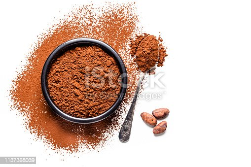 Top view of a black bowl filled with cocoa powder isolated on white background. A metal spoon with cocoa powder is beside the bowl and three cocoa beans are beside the bowl on the table. Useful copy space available for text and/or logo. Predominant colors are brown and white. High key DSRL studio photo taken with Canon EOS 5D Mk II and Canon EF 100mm f/2.8L Macro IS USM.