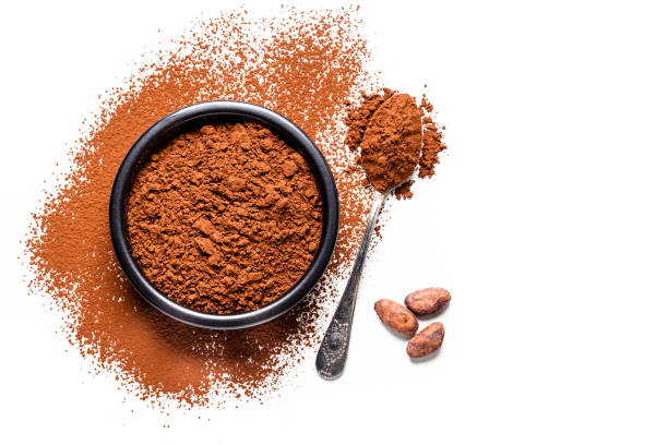 Cocoa powder with cocoa beans shot from above on white background Top view of a black bowl filled with cocoa powder isolated on white background. A metal spoon with cocoa powder is beside the bowl and three cocoa beans are beside the bowl on the table. Useful copy space available for text and/or logo. Predominant colors are brown and white. High key DSRL studio photo taken with Canon EOS 5D Mk II and Canon EF 100mm f/2.8L Macro IS USM. theobroma stock pictures, royalty-free photos & images