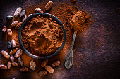 Top view of a black bowl filled with cocoa powder shot on abstract brown rustic table. A metal spoon with cocoa powder is beside the bowl and some cocoa beans are scattered on the table. Useful copy space available for text and/or logo. Predominant colors is brown. Low key DSRL studio photo taken with Canon EOS 5D Mk II and Canon EF 100mm f/2.8L Macro IS USM.